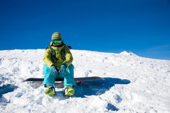 Snowboarder girl sitting. Young woman is on the snowboard against blue sky and snowy slope royalty free stock images