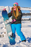 Snowboarder girl stands with snowboard. Stock Photos