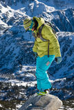 Snowboarder girl on the stone. Young woman in bright clothes is standing on a small rock royalty free stock photo