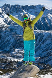 Snowboarder girl on the stone. Young woman in bright clothes is standing on a small rock and her hands up stock photography