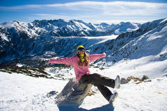 Snowboarder girl on the stone. Young woman in pink jacket and yellow cap against high mountains royalty free stock image