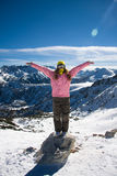 Snowboarder girl on the stone. Portrait of young woman in bright clothes standing on a small rock and her hands up royalty free stock photo