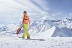 Snowboarder girl in a swimsuit walking on top of mountain Royalty Free Stock Photos