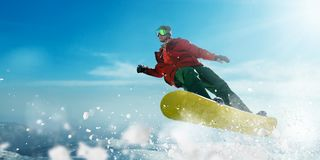 Snowboarder in glasses makes a jump, winter sport. Snowboarder in glasses makes a jump, sportsman in action. Winter active sport, extreme lifestyle. Snowboarding Royalty Free Stock Images