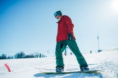 Snowboarder in glasses poses with board in hands. Blue sky and snowy mountains on background Royalty Free Stock Images