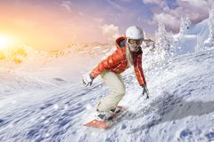 Snowboarder glides with high speed downhill through the powder snow. Snowboarder in orange hoodie and white pants glides on an orange snowboard over the fresh royalty free stock image