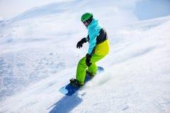 Snowboarder glissant en bas d'une pente Photo libre de droits