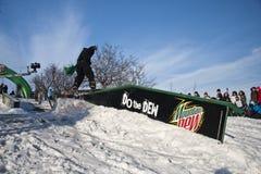 Snowboarder glissant sur le longeron à l'excursion de rosée Photographie stock libre de droits