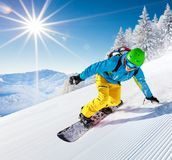 Snowboarder going downhill in high mountains Royalty Free Stock Photo