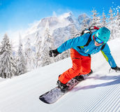 Snowboarder going downhill in high mountains Stock Photo
