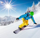 Snowboarder going downhill in high mountains Royalty Free Stock Images