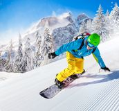Snowboarder going downhill in high mountains Royalty Free Stock Photography