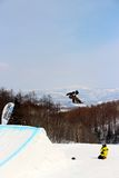 Snowboarder going off a big jump in hanazono park Stock Photo