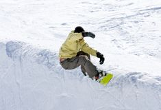 Snowboarder on half pipe of Pradollano ski resort in Spain. Snowy ski slopes of Pradollano ski resort in the Sierra Nevada mountains in Spain with snowboarder in Stock Photos