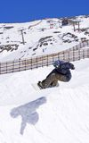 Snowboarder on half pipe of Pradollano ski resort in Spain. Snowy ski slopes of Pradollano ski resort in the Sierra Nevada mountains in Spain with snowboarder in Stock Images