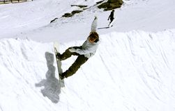 Snowboarder on half pipe of Pradollano ski resort in Spain. Snowy ski slopes of Pradollano ski resort in the Sierra Nevada mountains in Spain with snowboarder in Stock Image
