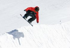 Snowboarder on half pipe of Pradollano ski resort in Spain. Snowy ski slopes of Pradollano ski resort in the Sierra Nevada mountains in Spain with snowboarder in Royalty Free Stock Photo