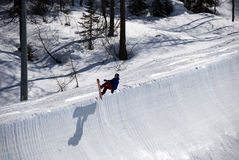 Snowboarder on half pipe trail. A snowboarder does a trick at the half pipe at Valmalenco - Italy Royalty Free Stock Images