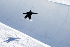 Snowboarder on half pipe trail. A snowboarder does a trick at the half pipe at Valmalenco - Italy Royalty Free Stock Photo