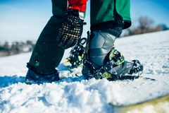 Snowboarder hand fastens snowboard fastening. Closeup. Winter active sport, extreme lifestyle, snowboarding Stock Photography
