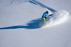 Snowboarder having fun in deep backcountry snow. Snowboarder freeriding down on fresh backcountry snow Stock Images