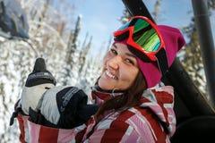 Snowboarder hermoso joven de la muchacha que sonríe y que muestra los pulgares para arriba Foto de archivo libre de regalías