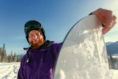 Snowboarder hold snowboard. On top of hill close up portrait Stock Images