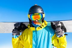 Snowboarder hold snowboard on top of hill. Close up portrait, snow mountains snowboarding on slopes Royalty Free Stock Image