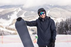 Snowboarder hold snowboard on top of hill close up portrait, snow mountains snowboarding on slopes. Ski resort. royalty free stock image