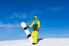 Snowboarder hold snowboard on top of hill Royalty Free Stock Photos