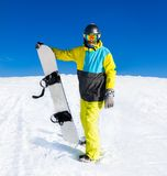 Snowboarder hold snowboard on top of hill Stock Photos