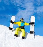 Snowboarder hold two snowboards sitting on snow Royalty Free Stock Photography