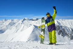 Snowboarder holding board in arms raised Stock Photography