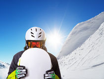 Snowboarder holding his snowboard off piste Stock Photography
