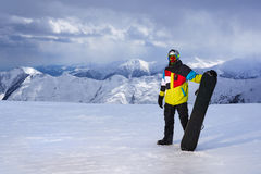 Snowboarder holding snowboard in hand on  background of mountains Royalty Free Stock Photos
