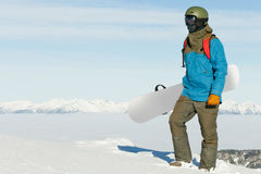 Snowboarder holding snowboard in hand and enjoying the landscape at the top of the mountain Royalty Free Stock Photos