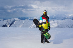 Snowboarder holding snowboard in hand standing in the snowfall Stock Images