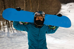 Snowboarder holding up plain board Stock Photography