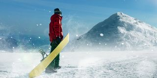 Snowboarder holds board in hands, winter sport. Snowboarder holds board in hands, blue sky and snowy mountains on background. Winter active sport, extreme Stock Image