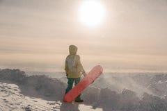 Snowboarder i sportswearanseende på bakgrunden av mounen Arkivbild