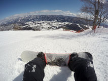 Snowboarder in the Japanese Alps. Snowboarder sitting on a slope and looking down at a snowy valley Stock Photo