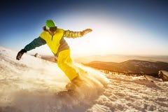 Snowboarder jedzie na skłon gór śnieżnym tle Zdjęcia Royalty Free