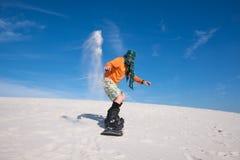 Snowboarder, jest ubranym szalika lądującego po sztuczki na piaska skłonie Obraz Royalty Free