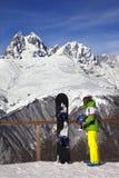 Snowboarder joven con el casco en manos y snowboard en viewpoin Fotografía de archivo libre de regalías