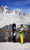 Snowboarder joven con el casco en manos y snowboard en viewpoin Imagenes de archivo