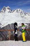 Snowboarder joven con el casco en manos y snowboard en viewpoin Fotos de archivo libres de regalías