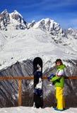Snowboarder joven con el casco en manos y snowboard en viewpoin Foto de archivo