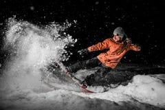 Snowboarder joven del freeride que salta en nieve en la noche imagen de archivo