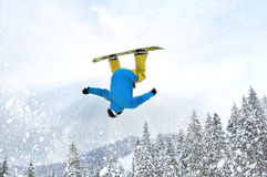 Snowboarder at jump inhigh mountains. At sunny day Stock Photos