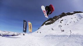 Snowboarder jump from springboard in front camera. Turning. Landscape. Blue sky stock video